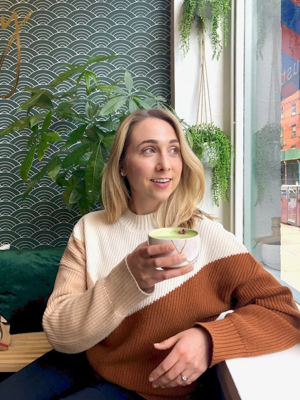 Girl drinking matcha by a window