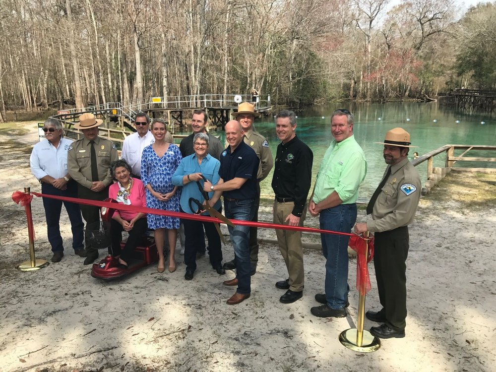 Officials (including Paula Russo, Traci Deen, Kim Davis, Noah Valenstein, Eric Draper, Kevin Brown, Cliff Maxwell, Gabby Paxton, and Jason Vickery) gathered on Feb. 9 to mark the grand opening of Gilchrist Blue Springs State Park. Photo by DEP