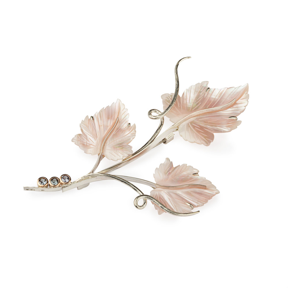 Carved mother of pearl leaves feature in this fabuluos design with colour change garnets in rose gold and silver a brooch