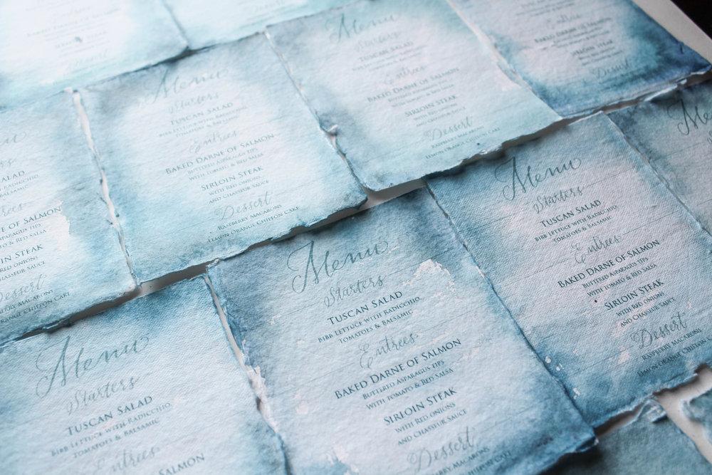 Teal wedding menus on handmade paper.