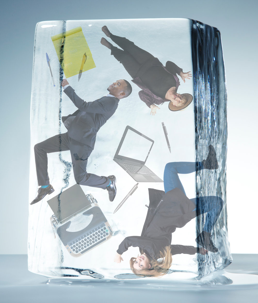 Writers, typewriters, laptops, and pens frozen in a block of ice