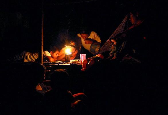 Enthusiasm for education is brought home to the jungle.   Here without electricity or running water, young students complete home-work by candle light.