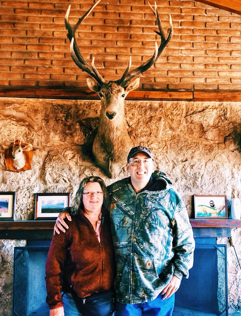 man and and woman posing infront of deer head