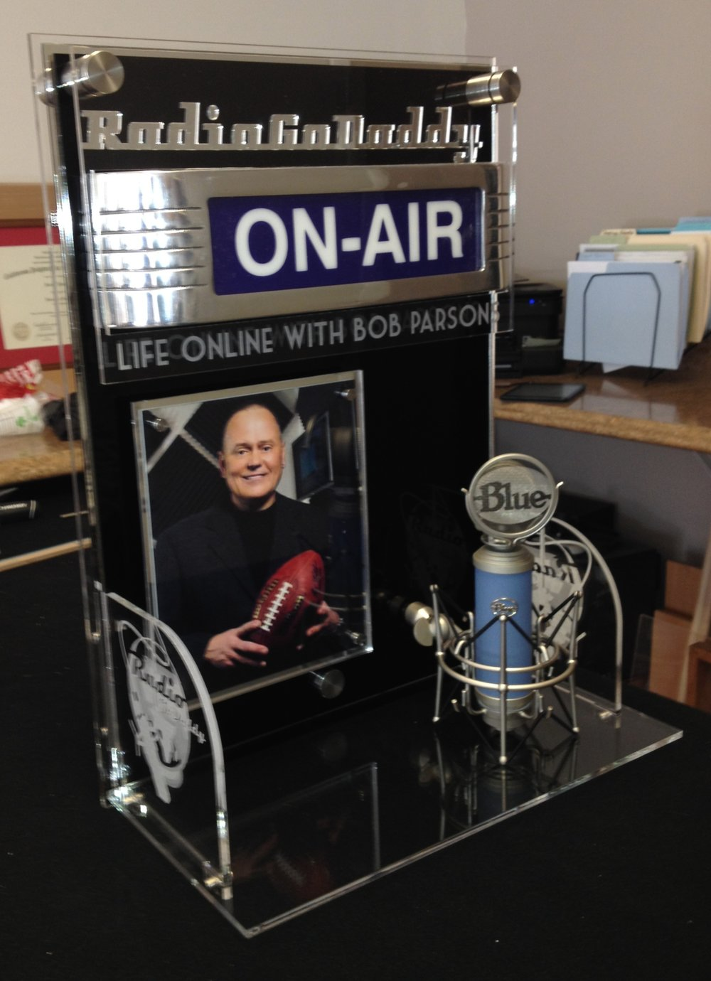 "Custom Alter - Presented to the Go-Daddy Corporate Founder, this alter features a 5x7 photograph, wired ""On-Air"" sign, microphone, custom acrylic relief and personalized etching  Contact us for design and pricing information."