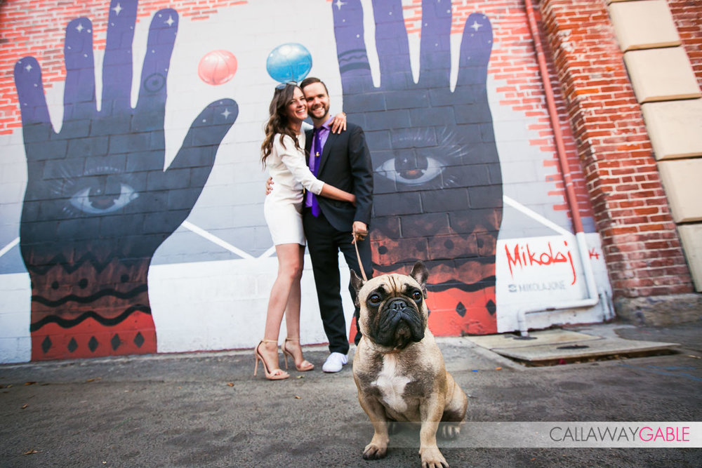 A portrait of our los angeles engagement couple's adorable pug dog in front of street art