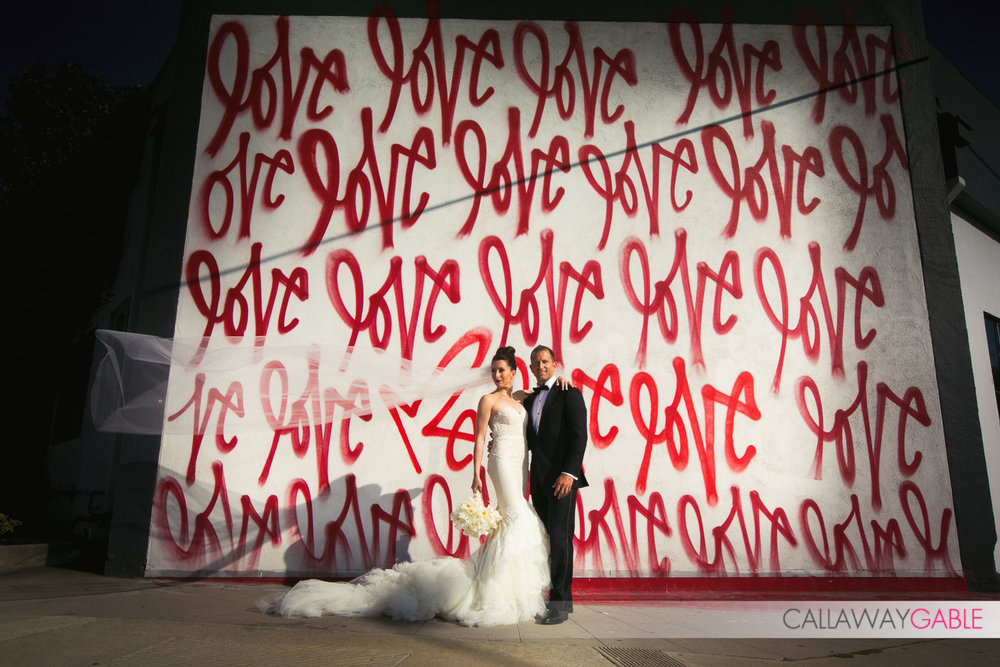 Bride and Groom in front of the Love wall in Culver City, blocks away from their Smog Shoppe Wedding