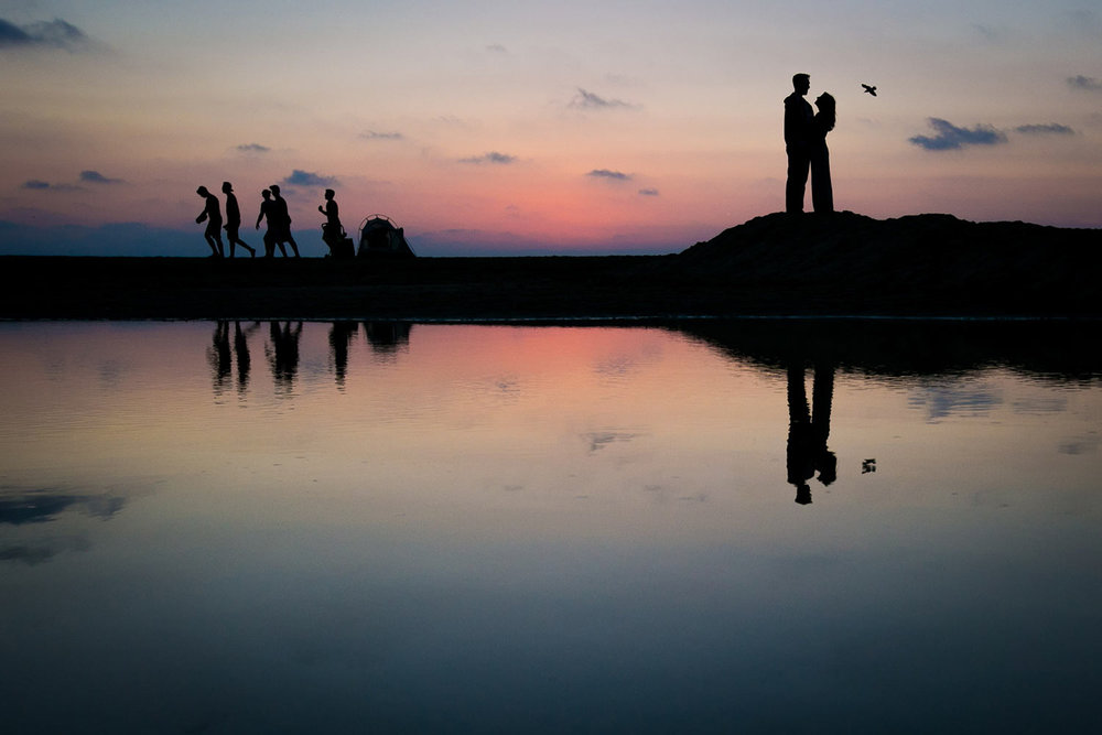 Sunset at Santa Monica Beach engagement photo with couple reflected in water