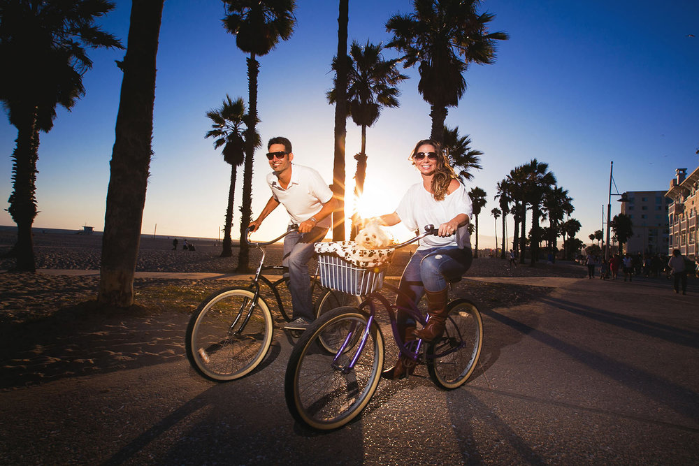 Fun Santa Monica Engagement Photo of Couple riding bikes at sunset