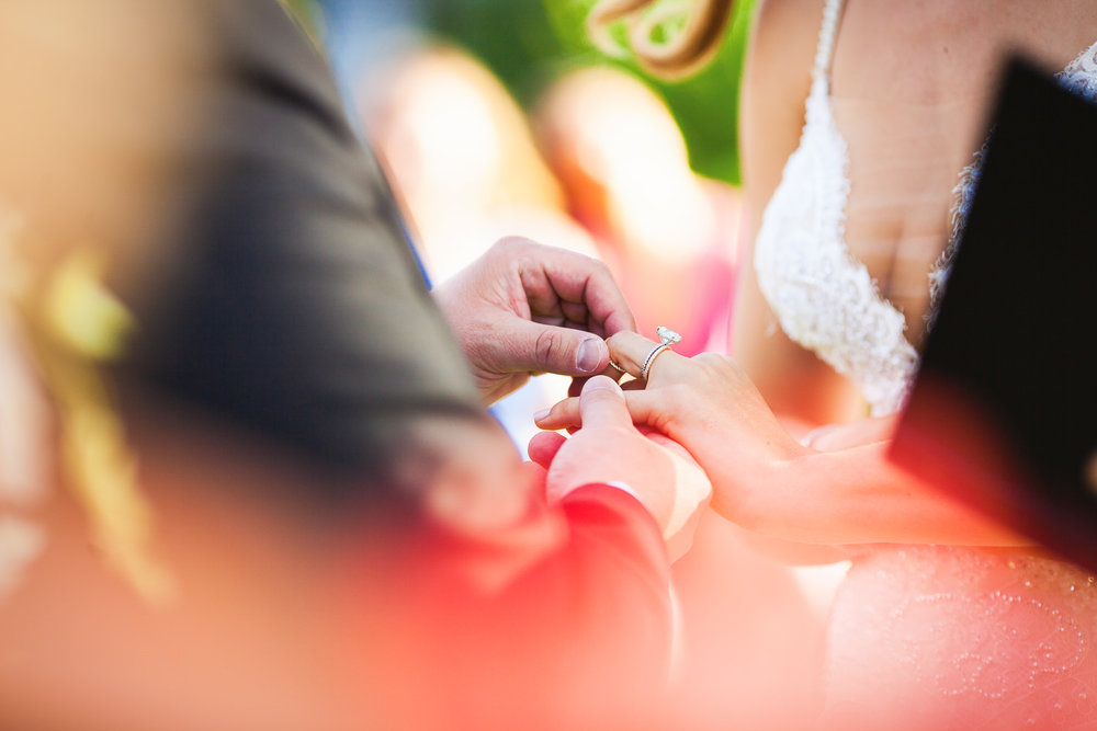 Ben putting the ring on Orian's finger at her Jewish wedding ceremony on the beach at the Four Seasons Hualalai
