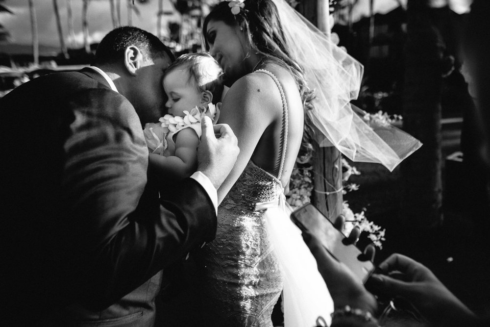 with their baby, Ben and Orian have a kiss under the chuppah by Big Island Wedding Photographer Callaway Gable