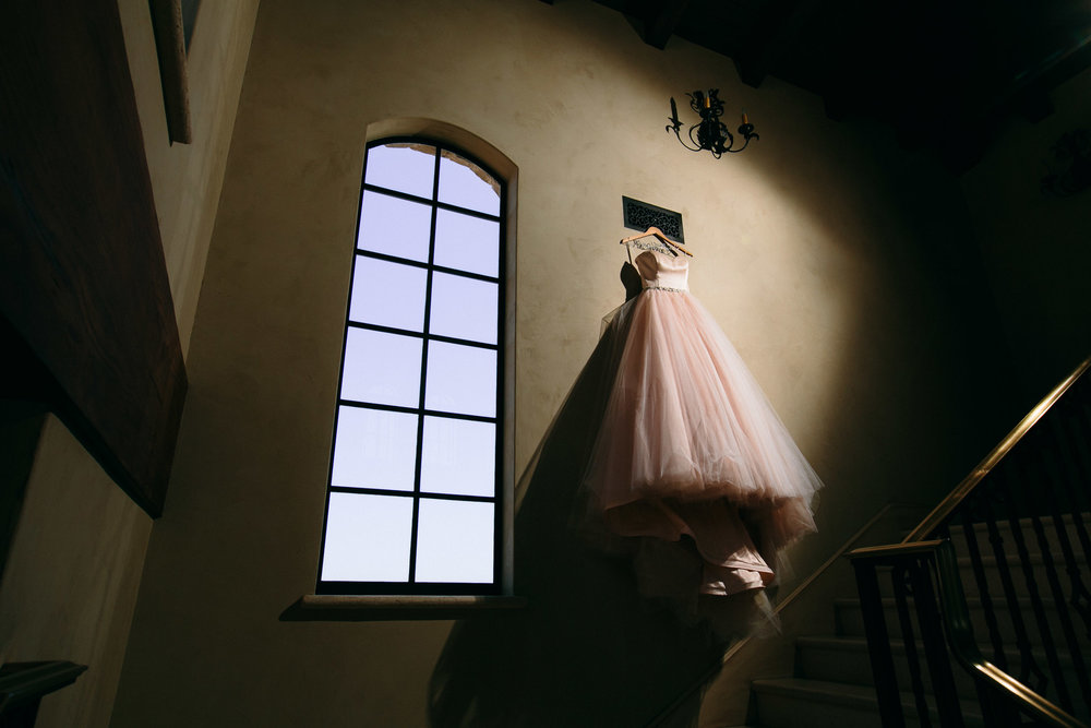 Malibu Rocky Oaks JLK Couture Wedding dress hanging in hallway