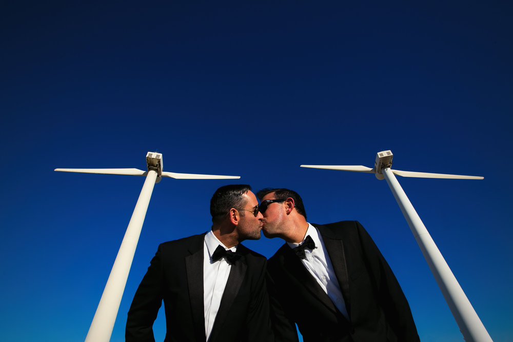 Same Sex Avalon Palm Springs Wedding - Kissing Under The Wind Turbines