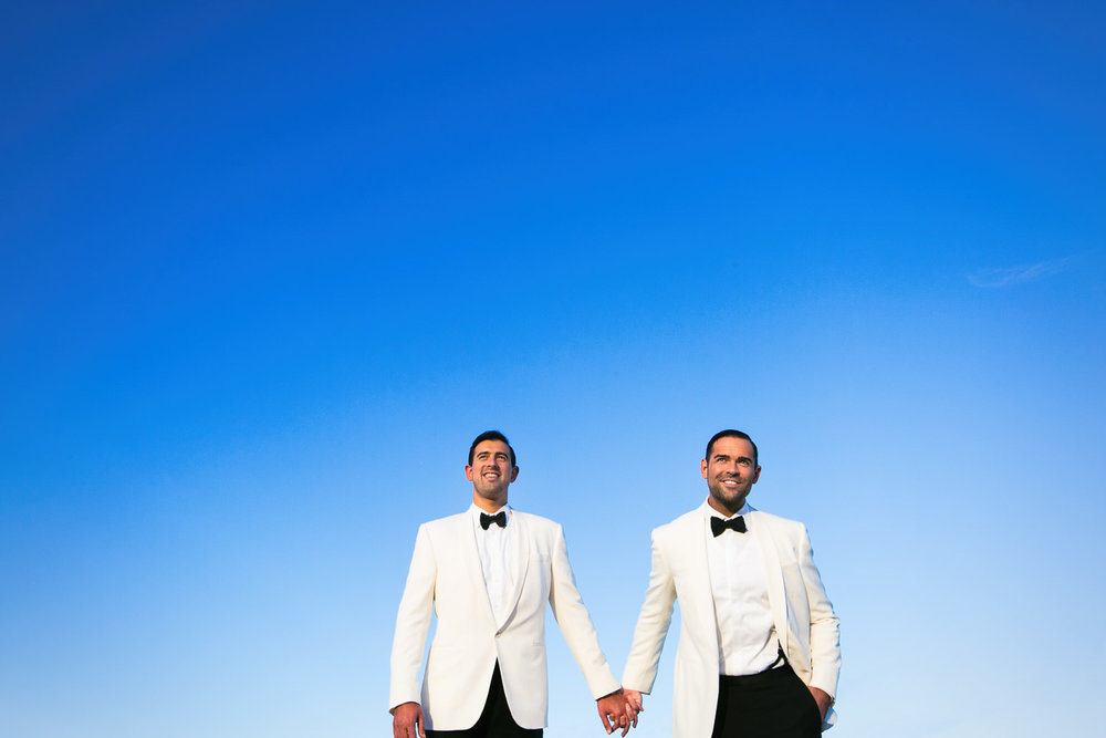 Same Sex Avalon Palm Springs Wedding - Holding Hands With Blue Sky Backdrop