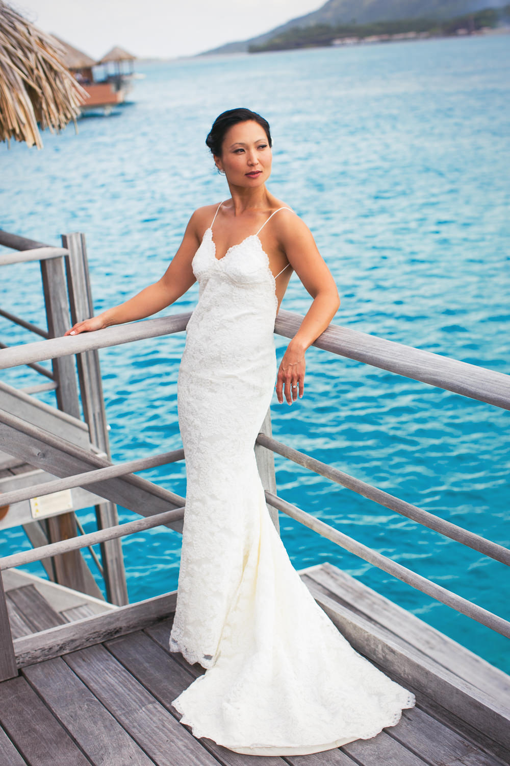 Four Seasons Bora Bora Wedding - Bride by the ocean in her wedding dress