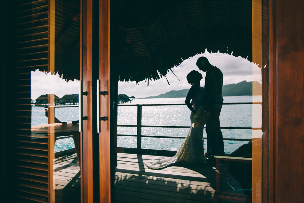 Four Seasons Bora Bora Wedding - Embracing through the window by the ocean