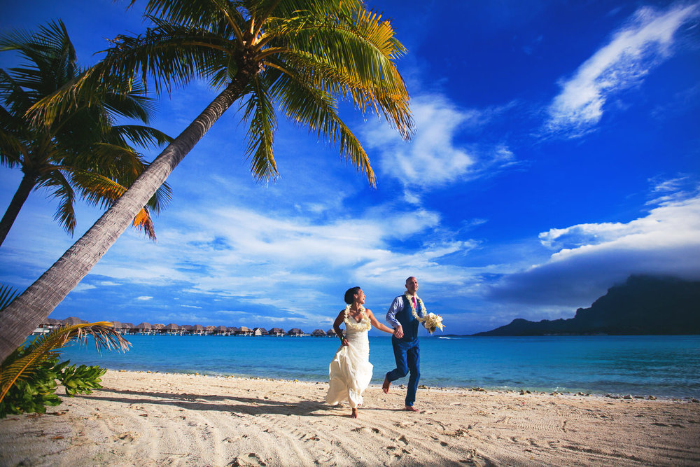 Four Seasons Bora Bora Wedding - Hand in hand running on the beach