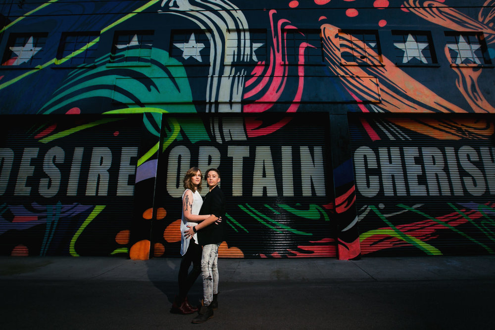 Same Sex Los Angeles Engagement - Holding each other by colorful wall