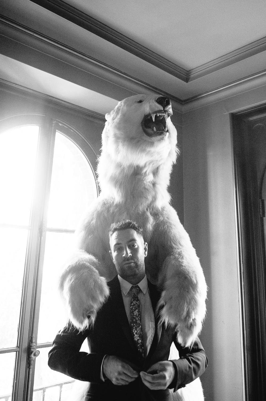 Rose McGowan Wedding at Paramour Estate - Groom posing under a stuffed polar bear