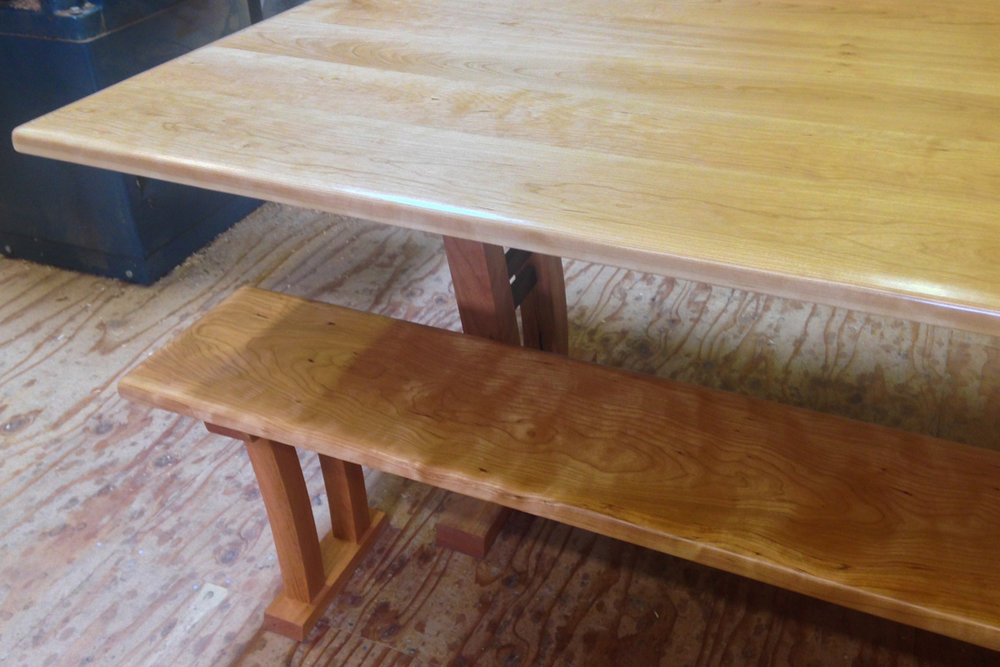Curly cherry table with arched legs and matching bench.