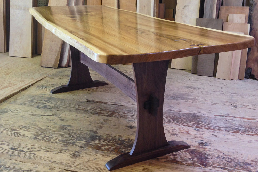 Live edge elm slab table top with a walnut trestle base.
