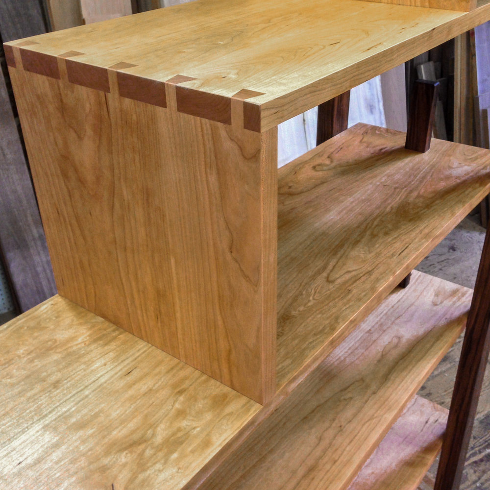 Detail of a stepped cherry shelving unit with dovetail corners, walnut legs and bookends.
