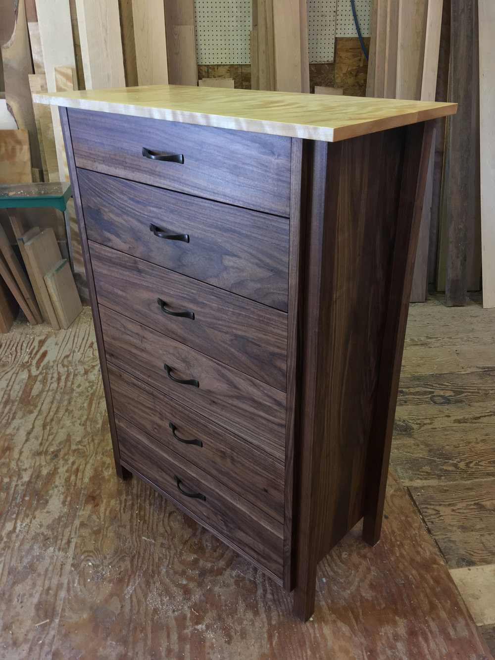 A flamed birch top on a 6 drawer walnut dresser.