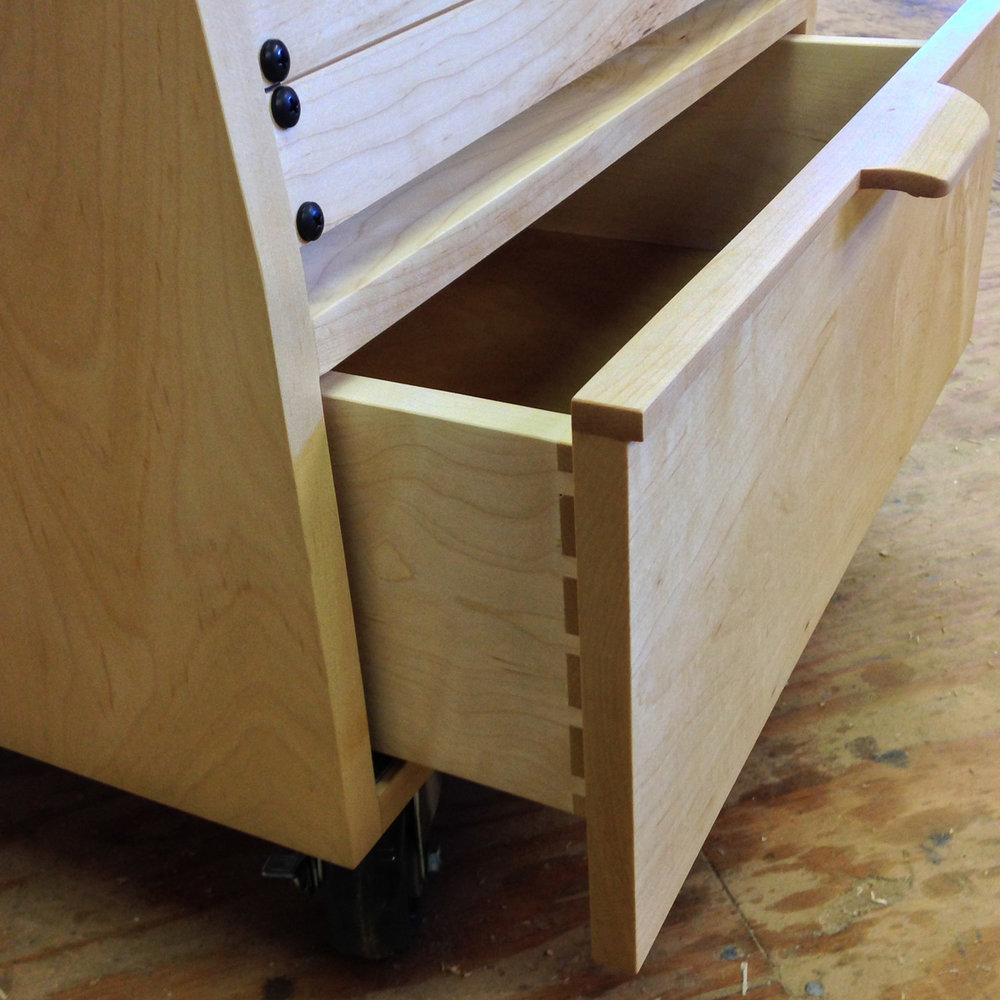 Detail of a lower drawer on a rolling recording studio equipment rack made from maple.