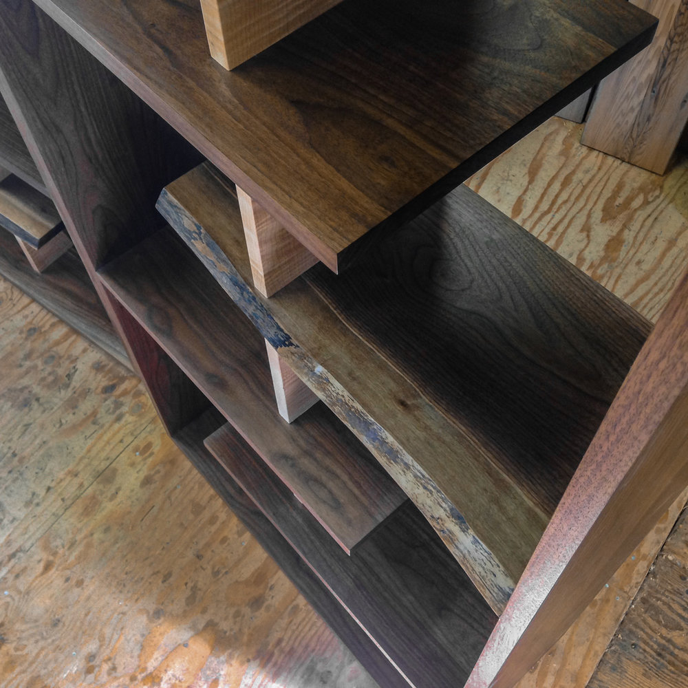Detail of a tiered bookshelf with dovetail case, and curly maple supports.