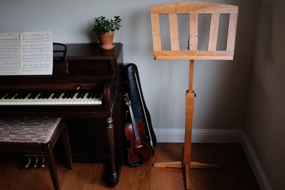 Cherry music stand with adjustable height and tilt. Featuring walnut and brass accents.