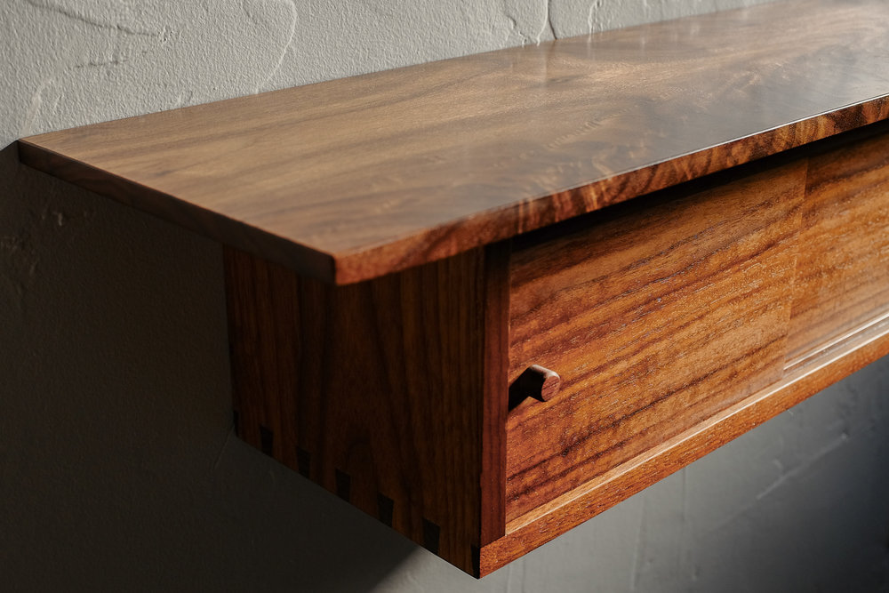 Detail of door and figured walnut grain on shelf.