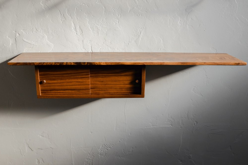 Hanging walnut box shelf with sliding pocket doors and a dovetail box.