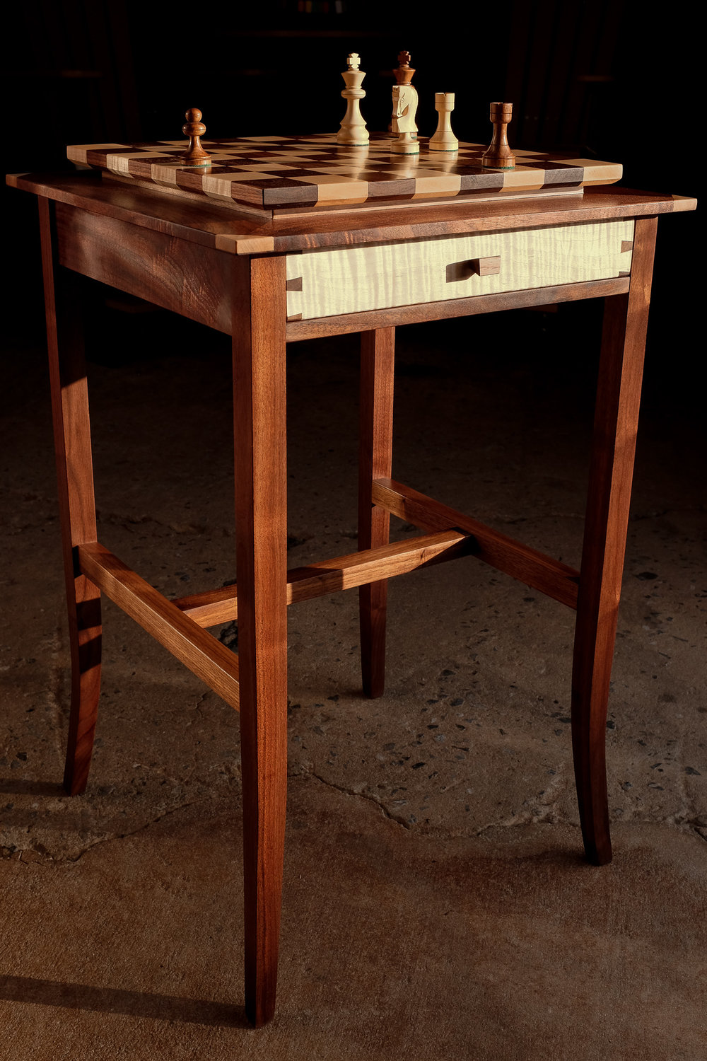 A chess table in walnut and curly maple. The playing surface is solid wood with internal joinery between each square and is friction fit in a floated mitered frame so it can be removed and used on another surface if preferred. The recessed walnut frame makes a perfect place for captured pieces. One drawer of maple with walnut sides, and one drawer of walnut with maple sides organizes the traditional Russian style pieces. Maple splines and angular wooden pulls tie it all together and make for an elegant experience.