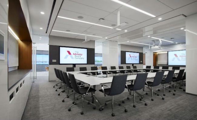 A divisible conference room with movable furniture can be oriented toward a display screen, a projection screen, or parted by a sky fold to create two separate conference areas.