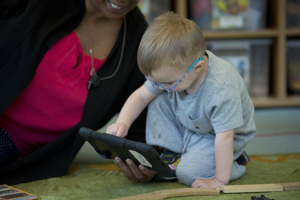 Young boy with glasses playing with Ipad with adult .jpg