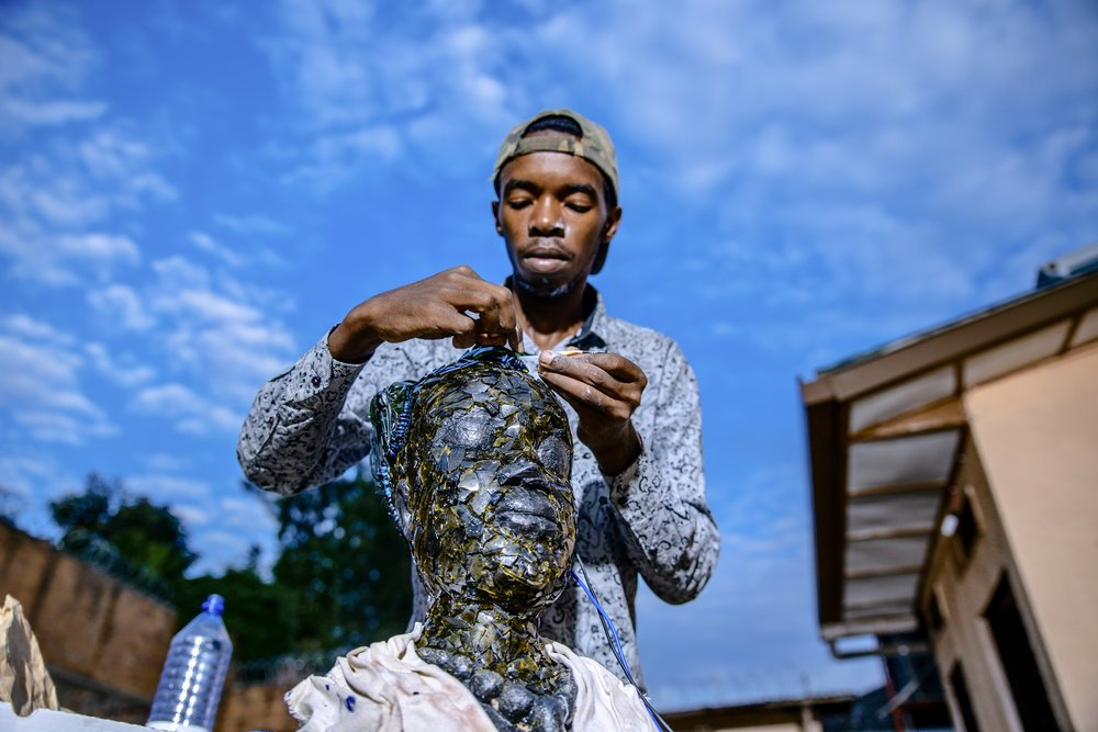 Remy adds superglue to a sculpture of a young Rwandan woman