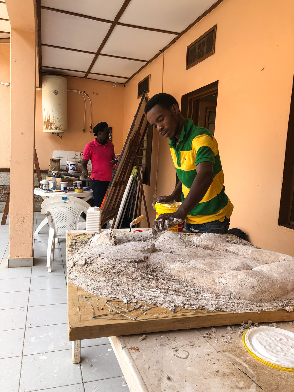 Remy lays down a mixture of plaster and sawdust to create a  sculpture