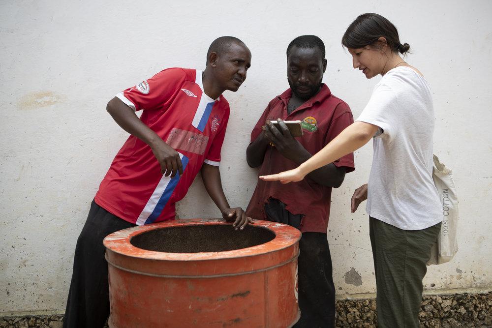 Karen bespricht mit dem Metallarbeiter Moresi und Samuel, wie der Kocher schlussendlich aussehen soll.