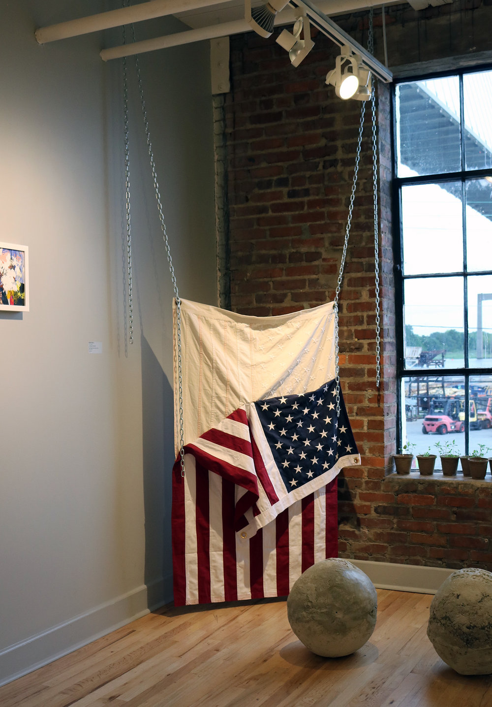 """#15 (Skinned)  Installation view United States flags, bleach, sinew, chain 84""""x60"""" 2017"""