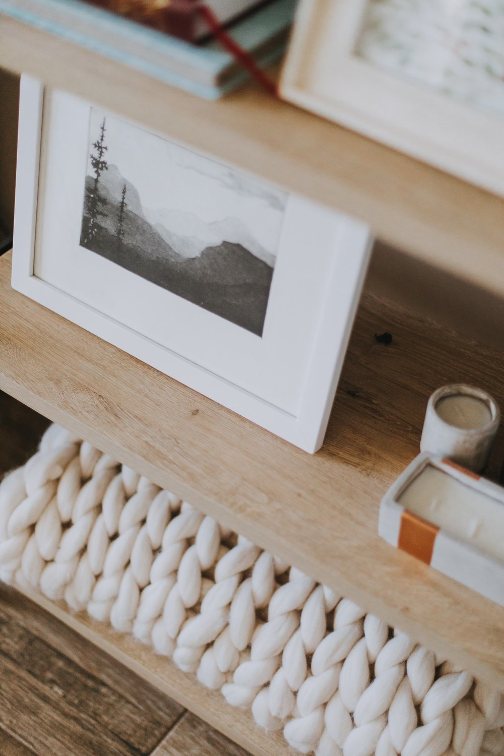 step 5— pictures - Add personality by including any of the following: photos of your family, a print of a favorite quote, or a beautiful or meaningful landscape. It's a good idea to choose frames that are cohesive with the rest of your shelf decor.