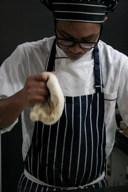 Filipino baker prepping Pandesal