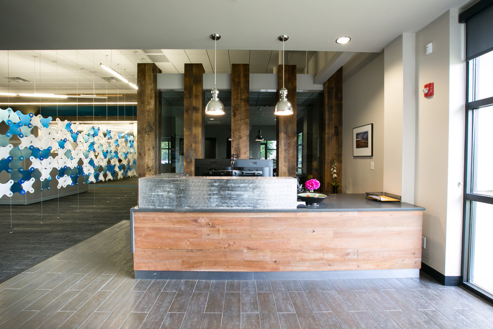 The front desk in the office lobby features brushed metal and reclaimed wood