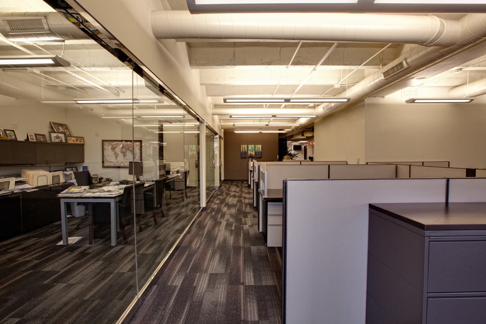 Glass-walled conference rooms and large cubicles fill CBC Real Estate's remodeled Country Club Plaza office