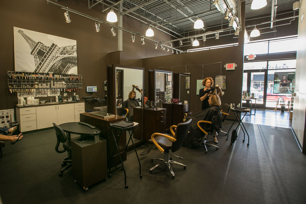 Stylists dress a woman's hair in the remodeled Salon Ami