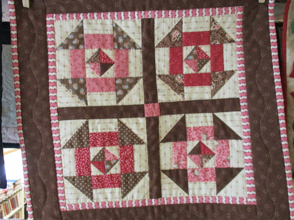 65, CHURN DASH (signed and dated), 18x18, Pieced by Susie Devos, Quilted by Fannie Frey