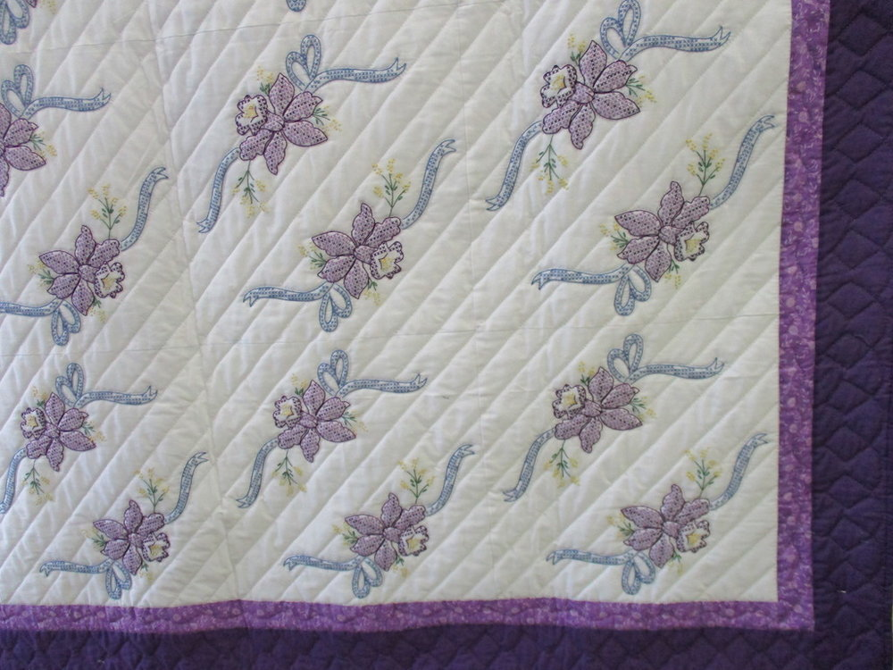 103, INTERLOCKING ORCHIDS QUILT AND 2 PILLOW SLIPS (SMALL SPOT ON FRONT, signed and dated), 80x80, Pieced by Nancy Cordell, Embroidered by Verna Eby, Quilted by Cora Horst