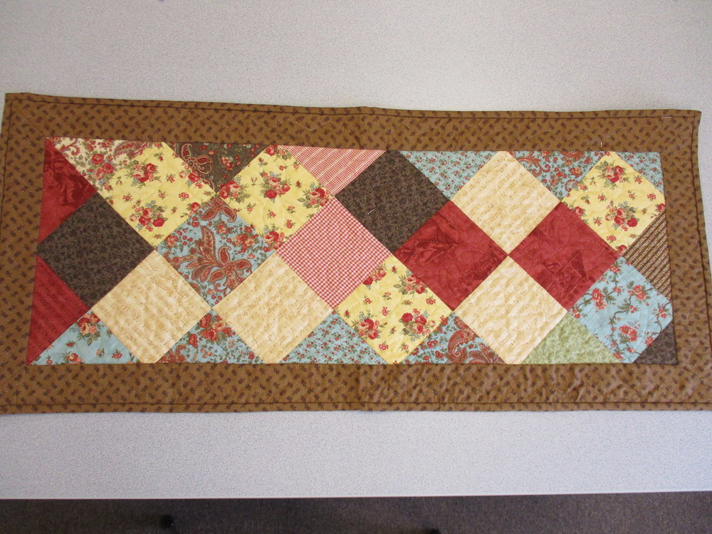 105, SAMPLER TABLE RUNNER (signed and dated), 18x42, Pieced by Karen Manderson, Quilted by Marie Eby
