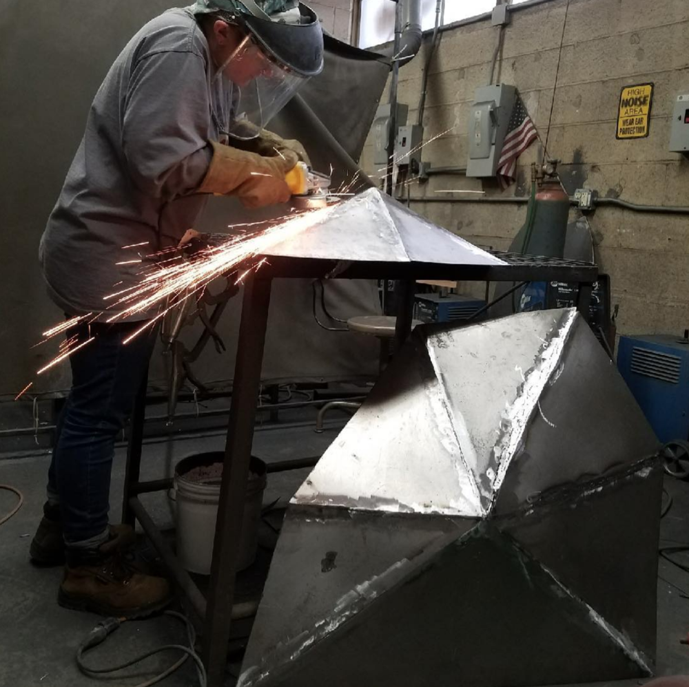 Photo by Sylvia Hardin  Liz sharpens the edges of her geometric sculpture  Cope,  a steel fabricated sculpture that incorporates 3d mapping.
