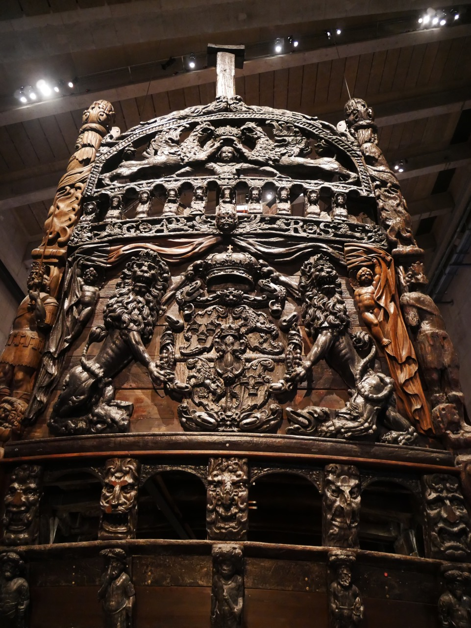 "The ornate stern of the ship. Description from the exhibit: ""The national coat of arms, Sweden's symbol. The lions have featured since the 13th century. The three crowns symbolize the Three Holy Kings. The central shield bears the arms of the Vasa family, a sheaf of corn, (""vase"" in old Swedish). The crown emphasizes the royal status of the dynasty."""