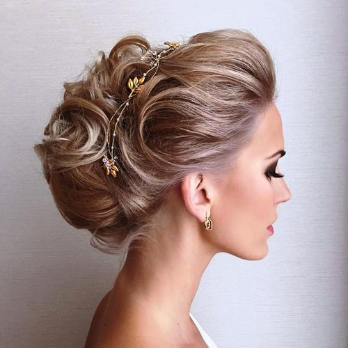 Teased updo with added touch of a floral hair accessory.