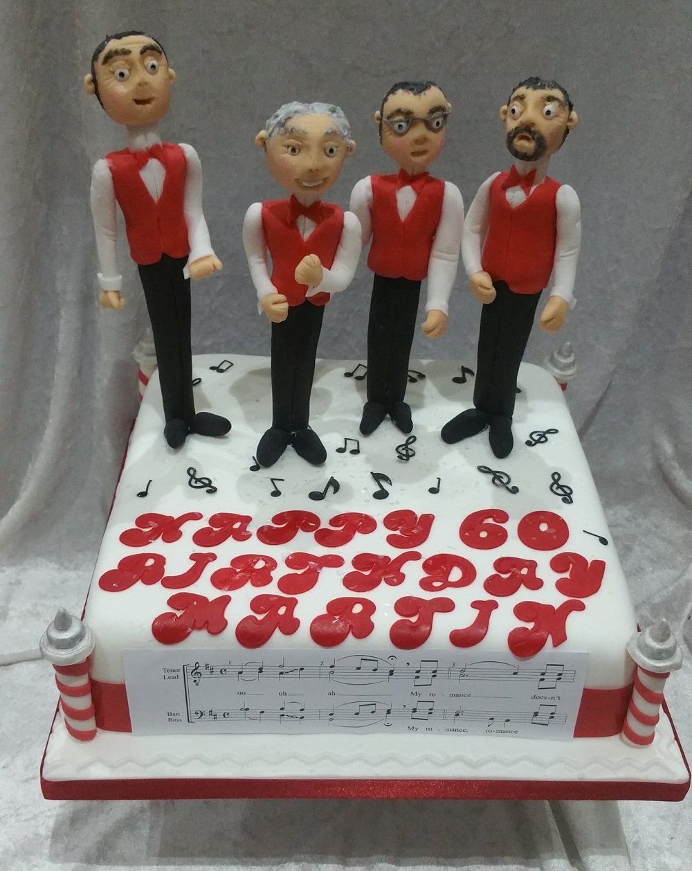 Barber's shop Cake - A fun cake for a passionate barber's shop singer.  Hand made figures of Martin and his friends, made to detail, together with musical notes of his favourite song and barber's shop poles.